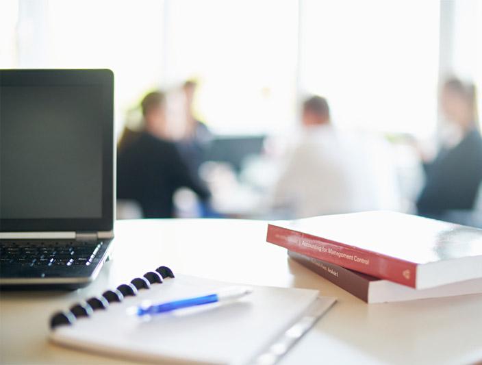 Ett bord med dator, pennor och böcker
